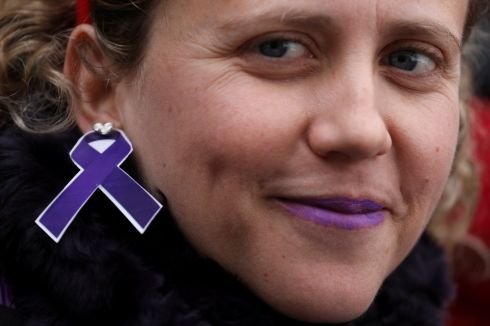 A woman wears an earring depicting a purple ribbon as she attends a nationwide feminist strike on International Women's Day in Madrid.  Photograph: Sergio Perez / Reuters