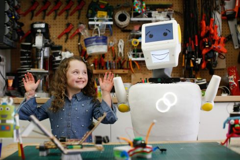 Brooke Walton (5) from Crumlin and Stevie the Robot, created by robotics engineers from Trinity College Dublin during an Engineers Week event in Dublin. Photograph:  Julien Behal