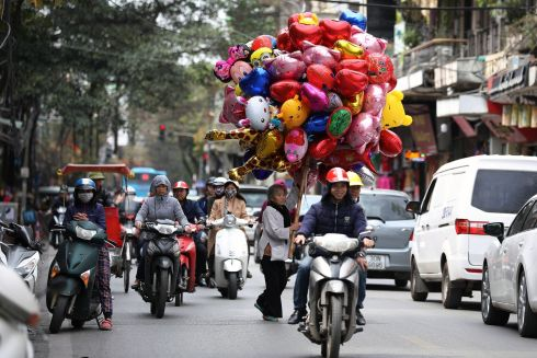 A street vendor selling balloons walks at a street in Hanoi, Vietnam, 08 March 2018. Flowers and balloons are considered the most popular gifts that men give women on International Women's Day in Vietnam. Photograph: Luong Thai Linh / Reuters