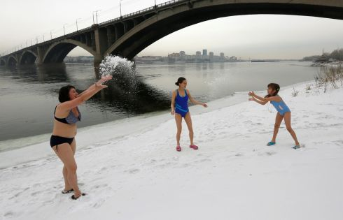 Pregnant Maria Timofeyenko (C), Anna Egorova and her 7-year old daughter Alexandra Sidorova, members of the Krepysh (Sturdy Person) family winter swimmers club, play in the snow on the bank of the Yenisei River during an event to mark International Women's Day in Krasnoyarsk, Russia. Photograph: Ilya Naymushin / Reuters
