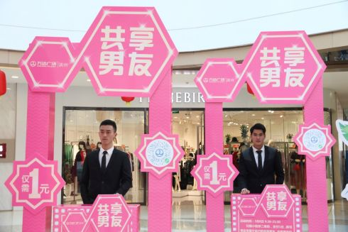 "Men stand behind booths during an International Women's Day event inside a shopping mall, where customers can rent a ""boyfriend"" for 30 minutes with one yuan (.16), in Binzhou, Shandong province, China. Photograph: Reuters"
