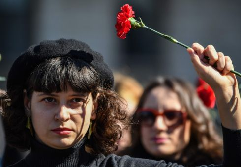 A women holds a flower as she protests against domestic violence in front of the Romanian Ministry of Interior in Bucharest.   Photograph: Daniel Michailescu  / AFP