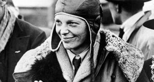 "In a June 26, 1928 photo, American aviatrix Amelia Earhart poses with flowers as she arrives in Southampton, England, after her transatlantic flight on the ""Friendship"" from Burry Point, Wales. Photograph: AP Photo"