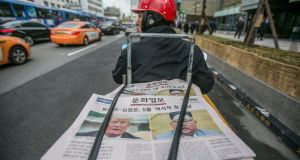 The Munhwa Ilbo newspaper featuring US president Donald Trump and North Korean leader Kim Jong-un in  a courier's motorcycle in Seoul, South Korea. Photograph: Jean Chung/Bloomberg