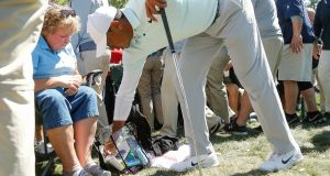 Tiger Woods removes his ball from a spectator's bag after hitting his second shot on the 18th hole during the second round of the Valspar Championship at Innisbrook Resort Copperhead Course  in Palm Harbor, Florida. Photograph:  Michael Reaves/Getty Images