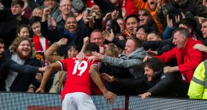 Marcus Rashford celebrates his first goal with the Manchester United fans. Photograph: