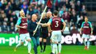 West Ham United defender James Collins  confronts a pitch invader carrying a corner flag during the  Premier League  match against Burnley at The London Stadium. Photograph: Ben Stansall/AFP/Gertty Images