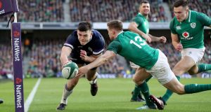 Scotland's Blair Kinghorn scores their  try despite the  tackle of Ireland's Garry Ringrose during the Six Nations  match at the Aviva Stadium. Photograph:  Bryan Keane/Inpho