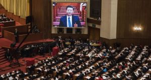 China's president, Xi Jinping, is seen on a large screen over delegates as he joins a session of the National People's Congress in Beijing on Sunday. Photograph: Kevin Frayer/Getty Images