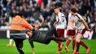 Burnley's English striker Ashley Barnes trips up a pitch invader during the Premier League clash between West Ham United and Burnley at The London Stadium. Photo: Ben Stansall/Getty Images