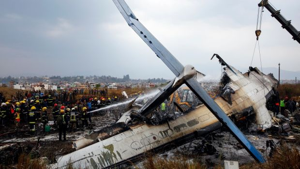 Firefighters work on the burning wreckage of US-Bangla Airlines Flight 211 while a crane is used amid ongoing rescue efforts at Tribhuvan International Airport in Kathmandu, Nepal, on Monday. Photograph: Narendra Shrestha/EPA