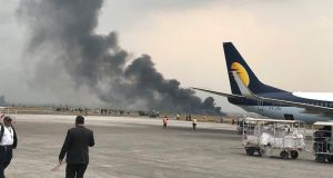 Smoke rises after a passenger plane travelling from Bangladesh crashed at the airport in Kathmandu, Nepal, on Monday. At least 49 people are confirmed dead. Photograph: Bishnu Sapkota/AP