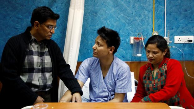 Sanam Shakya (33), a survivor of the US-Bangla plane crash, with his parents while undergoing treatment at a hospital in Kathmandu, Nepal. Photograph: Navesh Chitrakar/Reuters