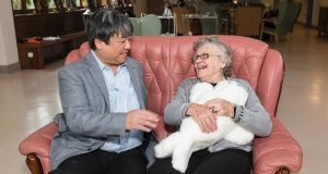 Dr Takanori Shibata, inventor of the therapeutic seal, Paro with a client in the Alzheimer Society of Ireland Orchard Day Care Centre, Blackrock, County Dublin.