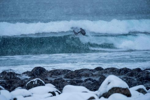A surfer rides a wave under snowfall on in Unstad, northern Norway, Lofoten islands, within the Arctic Circle. Photograph: Olivier Morin/AFP/Getty Images