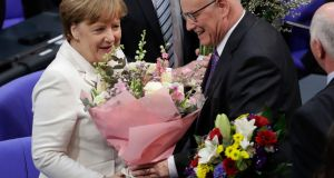 German Chancellor Angela Merkel receives flowers from the  Christian Democratic parliamentary group leader Volker Kauder after she was elected for a fourth term  in Berlin. Photograph: Michael Sohn/AP