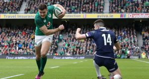 Jacob Stockdale runs past Blair Kinghorn to score his second  try against Scotland. Photograph:  Brian Lawless/PA Wire