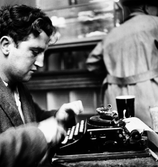 Brendan Behan at work in a bar. Photograph: Getty Images