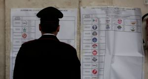 An Italian policeman looks at an electoral poster at a polling station in Rome. Why are Italian voters so disenchanted? The obvious answers are that economic performance has been so dismal, while established Italian policymakers appear so ineffective