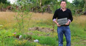 Funeral director Colin McAteer at Woodbrook Natural Burial Grounds, Killane, Co Wexford, with his own headstone. Photograph: Patrick Browne