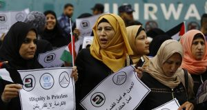 "Palestinian women hold signs in Arabic reading ""Refugees are the origin of the cause and the beginning of the tale"", during a demonstration outside the United Nations Relief and Works Agency (Unrwa) offices in Gaza City on Thursday. Photograph: Mohammed Abed/AFP/Getty Images"