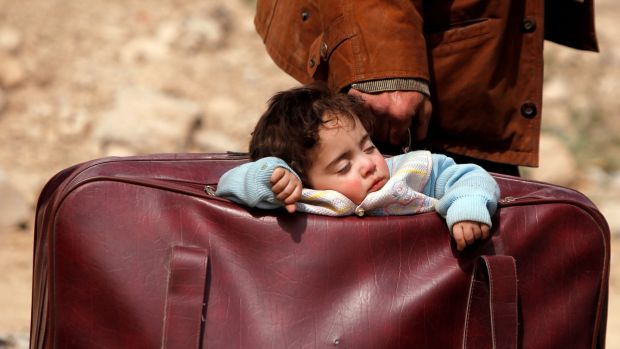 A child sleeps in a bag in the village of Beit Sawa, eastern Ghouta, Syria on Thursday. Photograph: Omar Sanadiki/Reuters