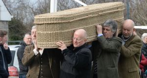Musicians Neil Martin and Christy Moore were among those to carry the coffin of uilleann piper Liam O'Flynn at his funeral in Kill, Co Kildare.  . Photograph: Alan Betson