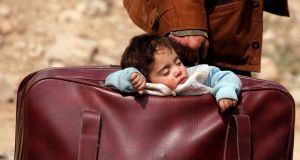 SYRIA: A child sleeps in a bag in the village of Beit Sawa, eastern Ghouta, Syria. Photograph: Omar Sanadiki/Reuters