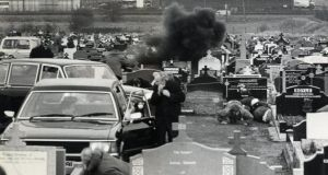 Mourners take cover as a grenade explodes during Michael Stone's attack in Milltown cemetery, Belfast, on March 16th, 1988. Photograph: Paddy Whelan