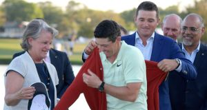 Rory McIlroy gets help putting on the championship sweater by Arnold Palmer's grandson, Sam Saunders, right, and his widow, Kit Palmer, left, after winning the Arnold Palmer Invitational. Photo: Phelan M. Ebenhack/AP Photo