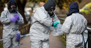 Police officers in protective suits and masks work near the scene where Sergei Skripal and his daughter Yulia were discovered after being attacked with a nerve agent in Salisbury. Photograph: Jack Taylor/Getty Images