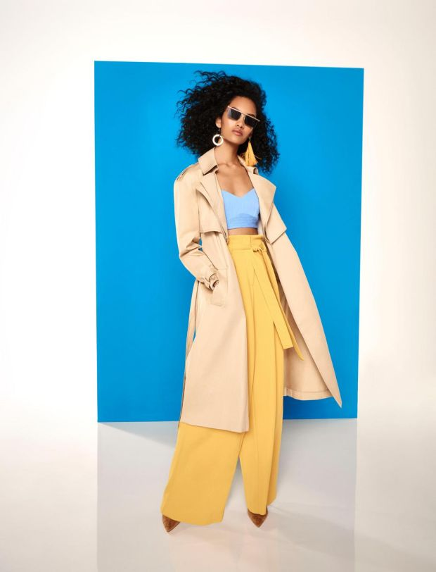 Trench coat €113, blue bra top €37, earrings €17, sunglasses €22, trousers €60, boots €75, all from River Island