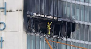 BALLYMUN BLAZE: A firefighter surveys the damage at the Metro Hotel, Ballymun, on Friday morning. Photograph: Colin Keegan/Collins Dublin