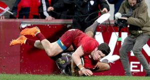 Alex Wootton scores Munster's key third try against the Scarlets as Tom Varndell makes the tackle. Photograph: Dan Sheridan/Inpho