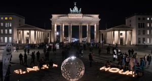 A glowing globe and the words Earth Hour pictured in front of the unlit Brandenburg Gate shortly after the beginning of the international Earth Hour in Berlin. Photograph: Paul Zinken/AFP/Getty Images