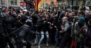 Catalan Mossos d'Esquadra regional police officers clash with pro-independence supporters trying to reach the Spanish government office in Barcelona on Sunday. Photograph: Felipe Dana/AP