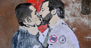 A mural in Rome depicting Five Star Movement leader Luigi Di Maio  kissing League leader Matteo Salvini in the context of their striking a deal. Photograph: Tiziana Fabi/AFP/Getty Images