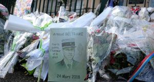 Tributes to Arnaud Beltrame killed in jihadist attack are pictured in front of barracks of the gendarmerie on Wednesday. in Carcassonne.  Photograph: Eric Cabaniseric/AFP/Getty