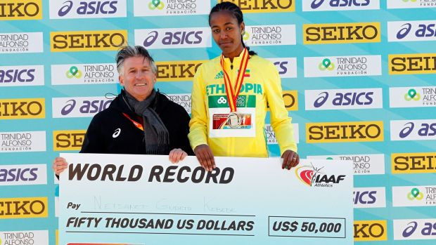 Ethiopia's Netsanet Gudeta Kebede receives a €50.000 cheque for setting a new world record time of 1:06.11 hours at the Women's World Half Marathon from IAAF president Sebastian Coe in Valencia. Photograph: Miguel Angel Polo/EPA