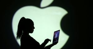 Silhouette of laptop user is seen next to a screen projection of Apple logo. Apple has released a software update across all platforms to bring its services fully into line with the new GDPR (General Data Protection Regulation) rules.  PHOTOGRAPH: Dado Ruvic/Reuters
