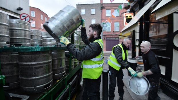 Darragh Gavin and Paul Reid from Heineken with Darragh Ridgeway. utilities manager of Slatterys Pub on Capel Street, making the first delivery to the pub on a Good Friday since 1922. Photograph: Alan Betson / The Irish Times