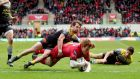 Scarlets' Rhys Patchell scores his side's opening try despite the tackle of  Arthur Retiere of La Rochelle during the Champions Cup quarter-final at Parc y Scarlets.  Photograph: James Crombie/Inpho