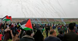 Palestinians fleeing as tear gas grenades begin to drop during a demonstration near the border with Israel east of Gaza City to commemorate Land Day. Photograph: Mahmud Hamsmahmud/ AFP /Getty Images
