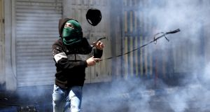 A Palestinian protester hurls back a tear gas grenade fired by Israeli troops, during clashes in the West Bank city of Hebron on Saturday. Photograph: Abed al Hashlamoun/EPA