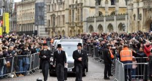 The hearse containing Prof Stephen Hawking's remains arrives at University Church of St Mary the Great in Cambridge as mourners look on. Photograph: PA