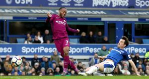 Manchester City's Raheem Sterling scores his side's third goal despite the challenge of Everton's Leighton Baines during the  Premier League match at Goodison Park. Photograph:  Tim Goode/PA Wire
