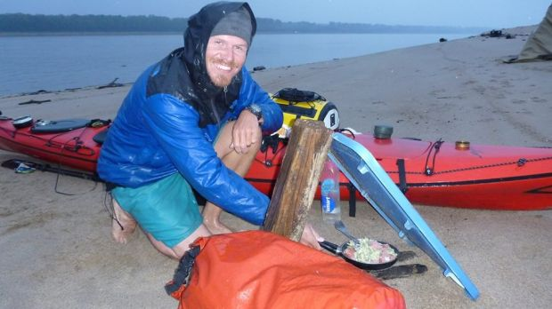 Henk van der Klok cooking dinner in the rain on the banks of the Mississippi, during a source to sea paddle of the entire river