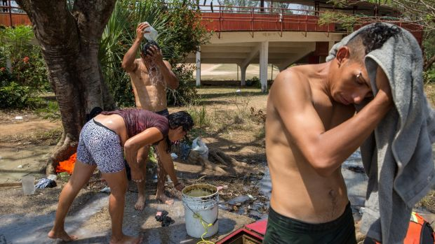 Migrants wash up at a temporary camp in Matías Romero. Photograph: Brett Gundlock/The New York Times