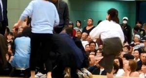 A screenshot from a YouTube video shows women climbing up a sumo ring to treat  city mayor Ryozo Tatami,  in a gym in Maizuru, Kyoto prefecture, Japan. Photograph: Kyodo/via Reuters