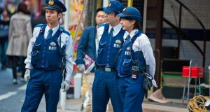 Japanese police officers standing on a Tokyo street. Photograph: iStock